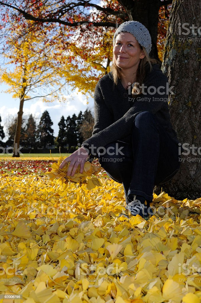 Women in park surrounded by autumn leaves, royalty-free stock photo