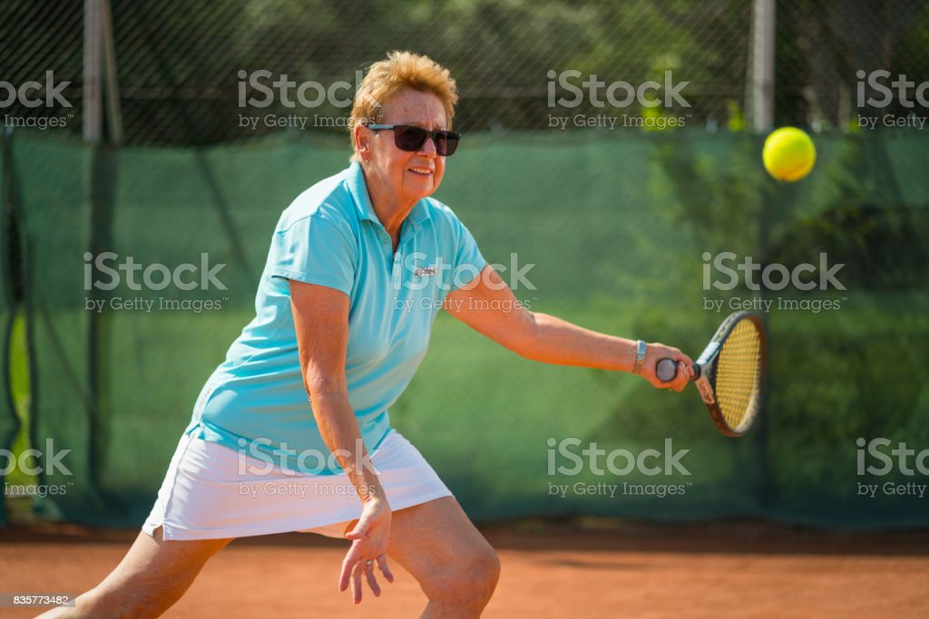Women in Sport, 70 years old active woman playing tennis stock photo