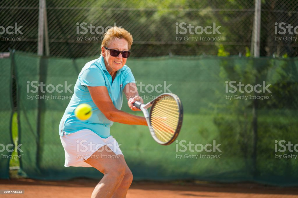 Women in Sport, happy smiling senior woman playing tennis outdoors in summer stock photo