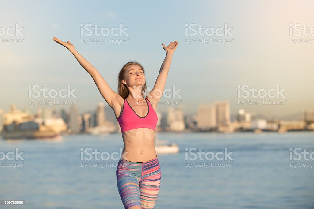 Women In Sports Bra With Arms Raised In Happiness stock photo