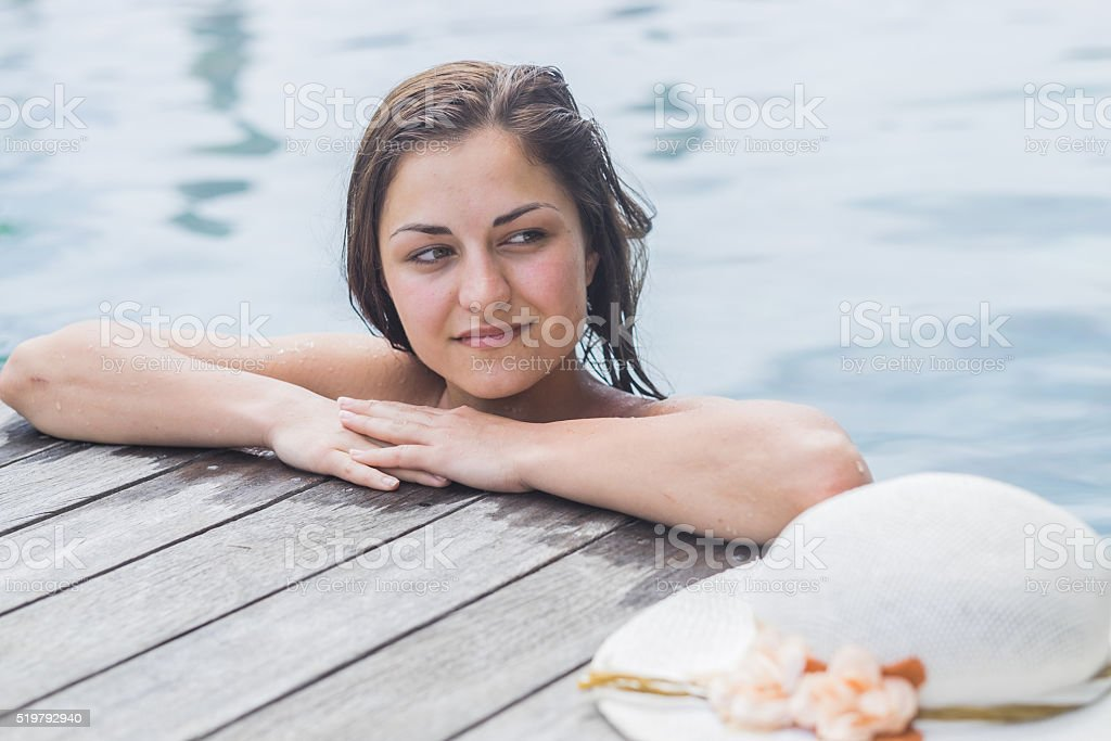 women in the pool with hat on side stock photo