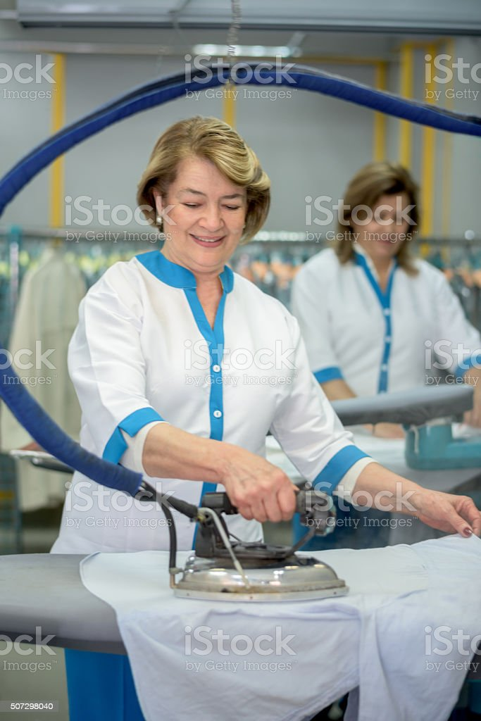 Women ironing clothes at a laundry shop stock photo