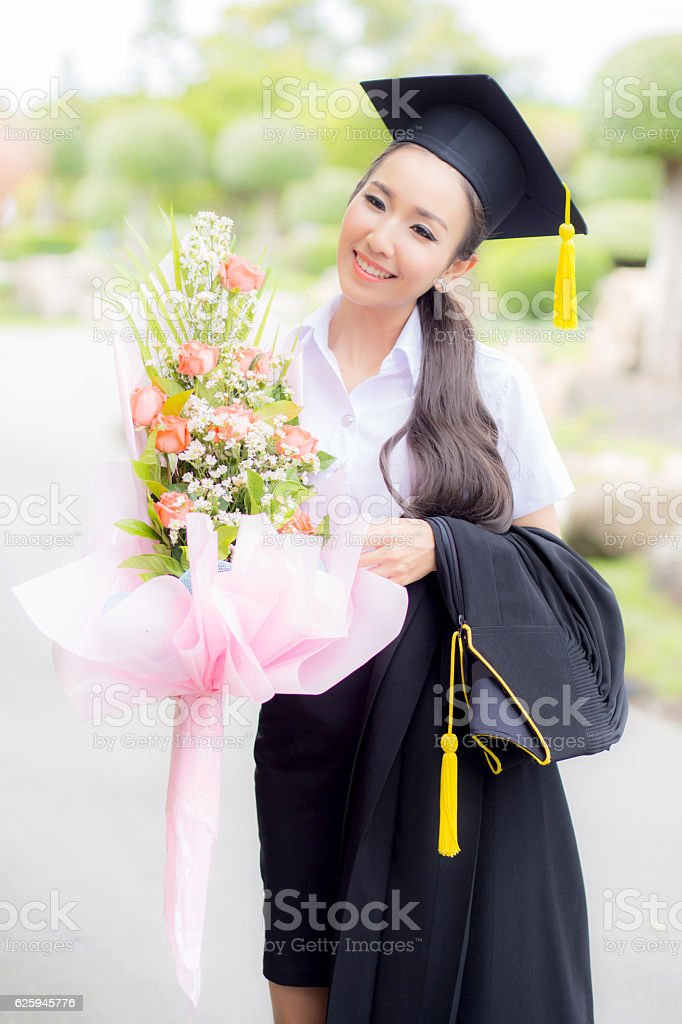 women is a Graduate holding a bouquet and smile stock photo