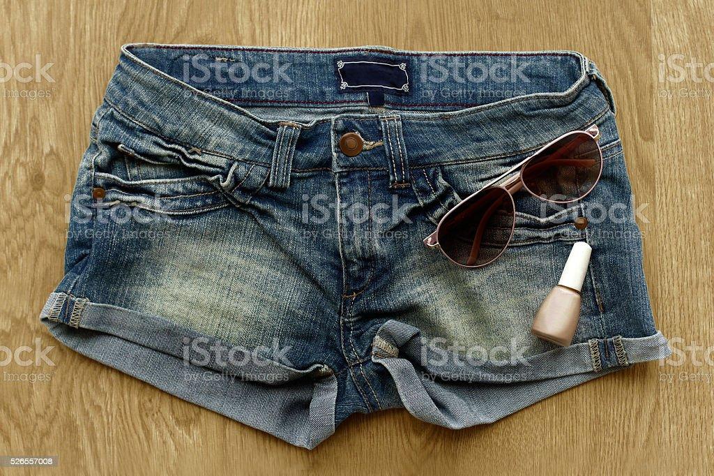 Women jeans shorts, nail polish and sunglasses stock photo