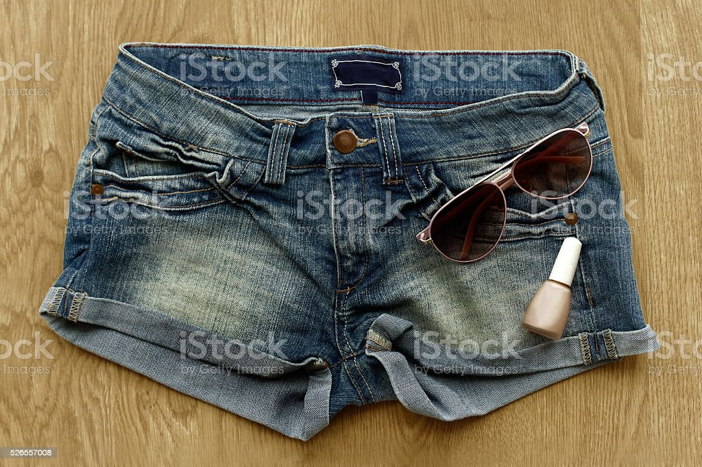Women jeans shorts, nail polish and sunglasses stock photo