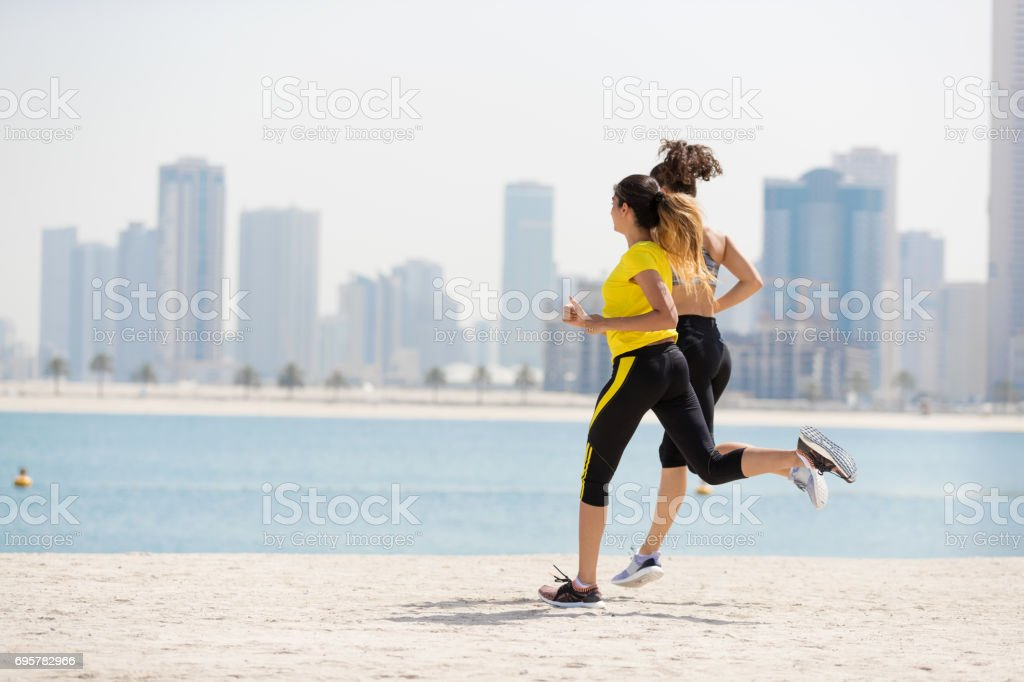 Women jogging with cityscape in background stock photo