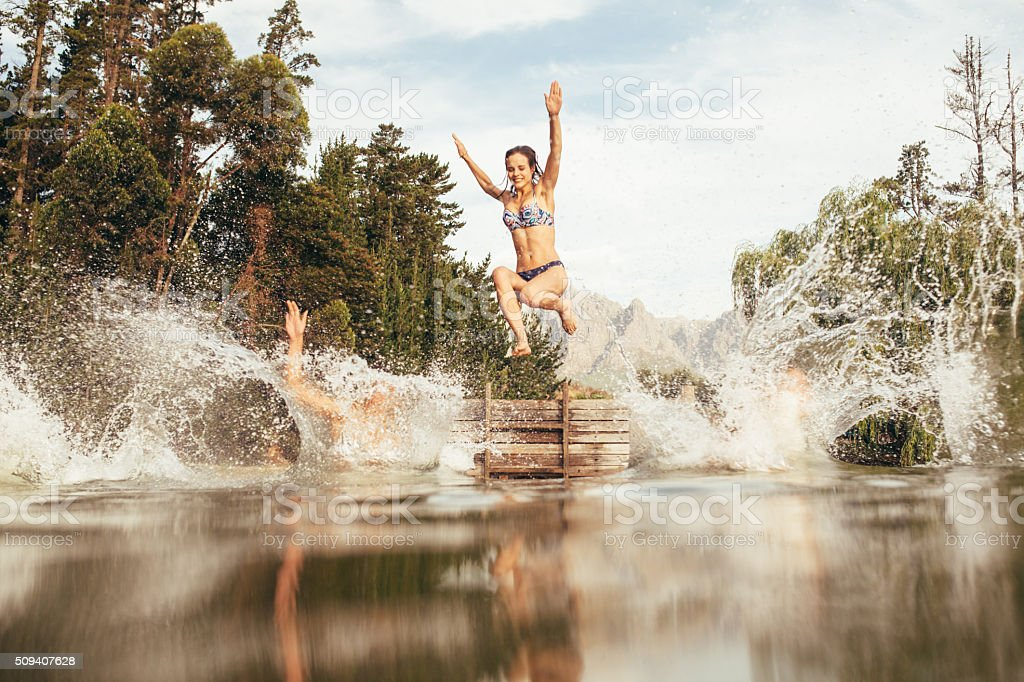 Women jumping into a lake from jetty stock photo
