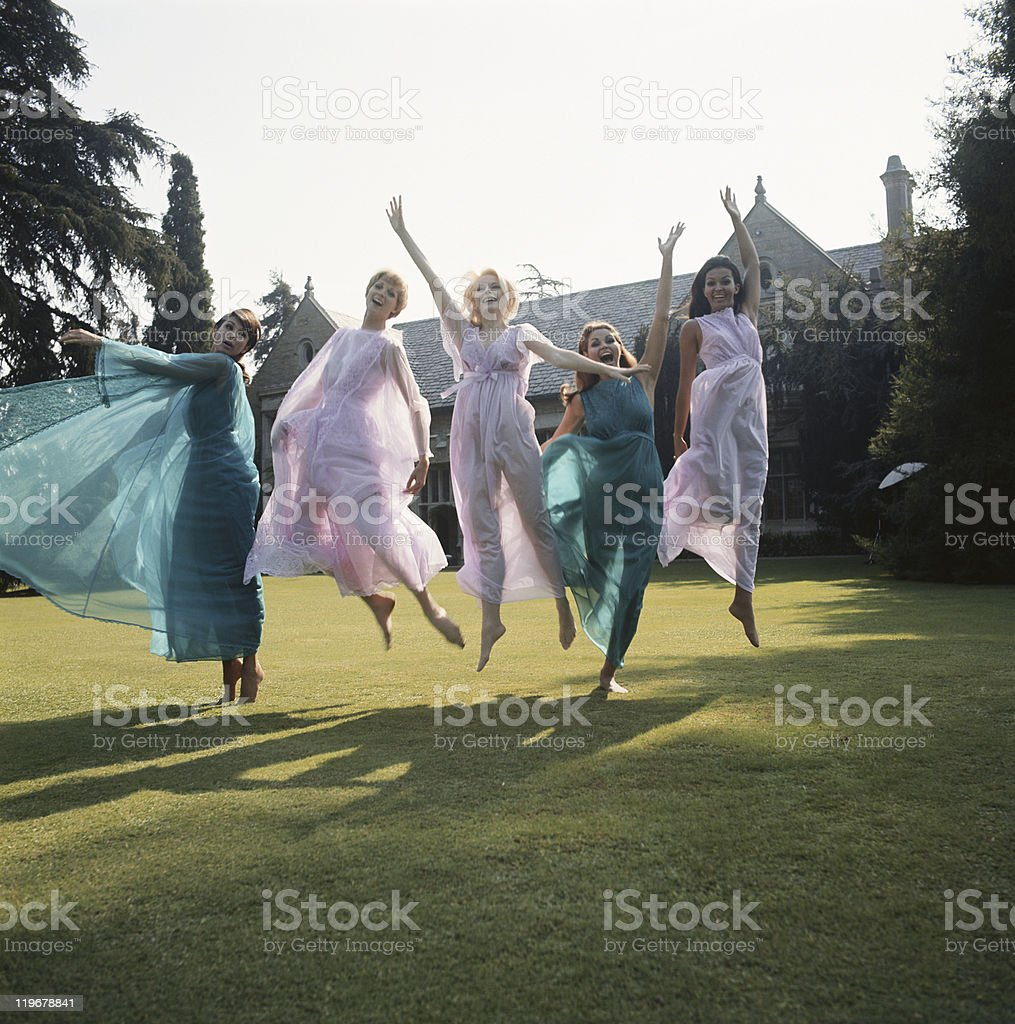 Women jumping on lawn stock photo