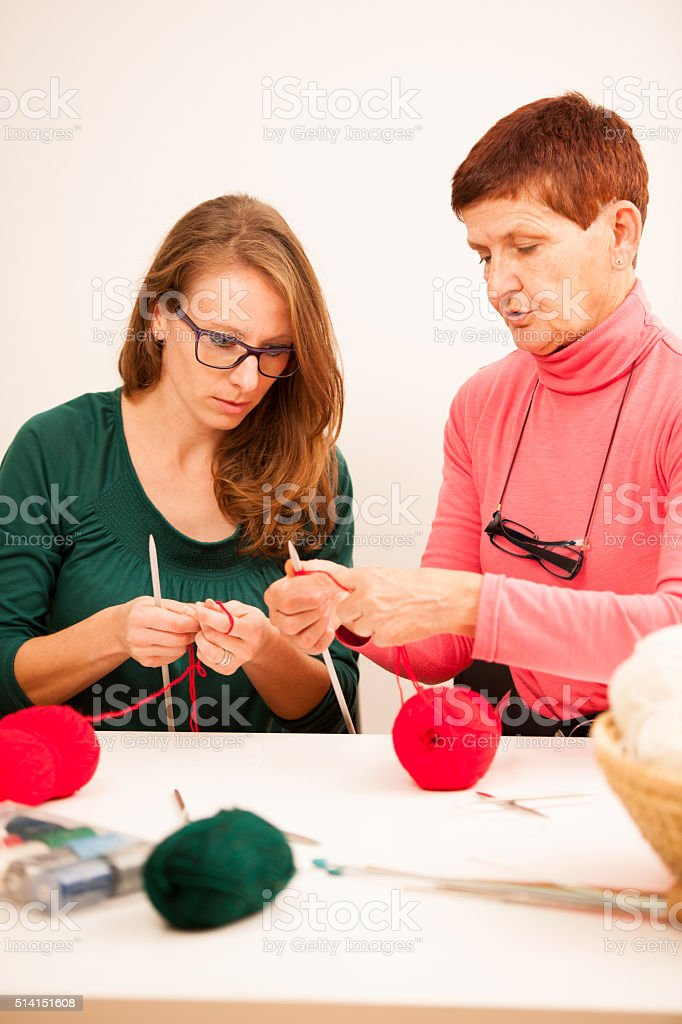 Women knitting with red wool. Eldery woman transfering her knowledge stock photo
