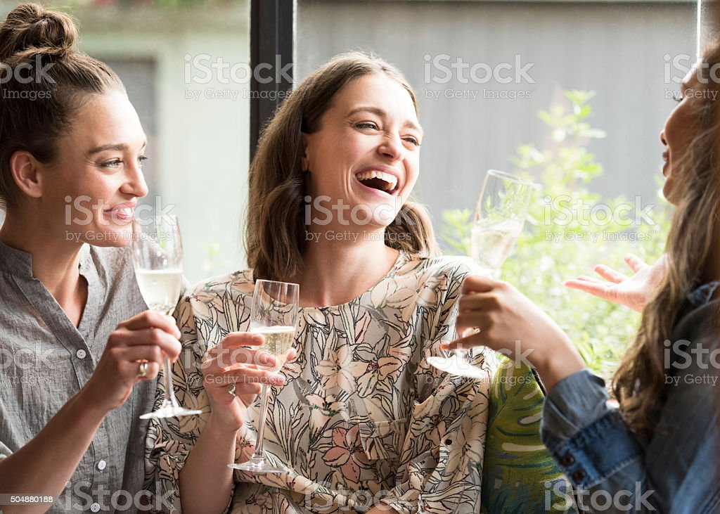 Women laughing in bar with wine glasses stock photo