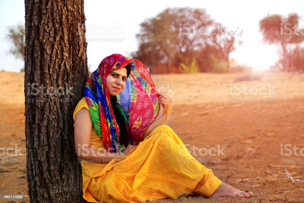 Women leaning against the tree trunk stock photo