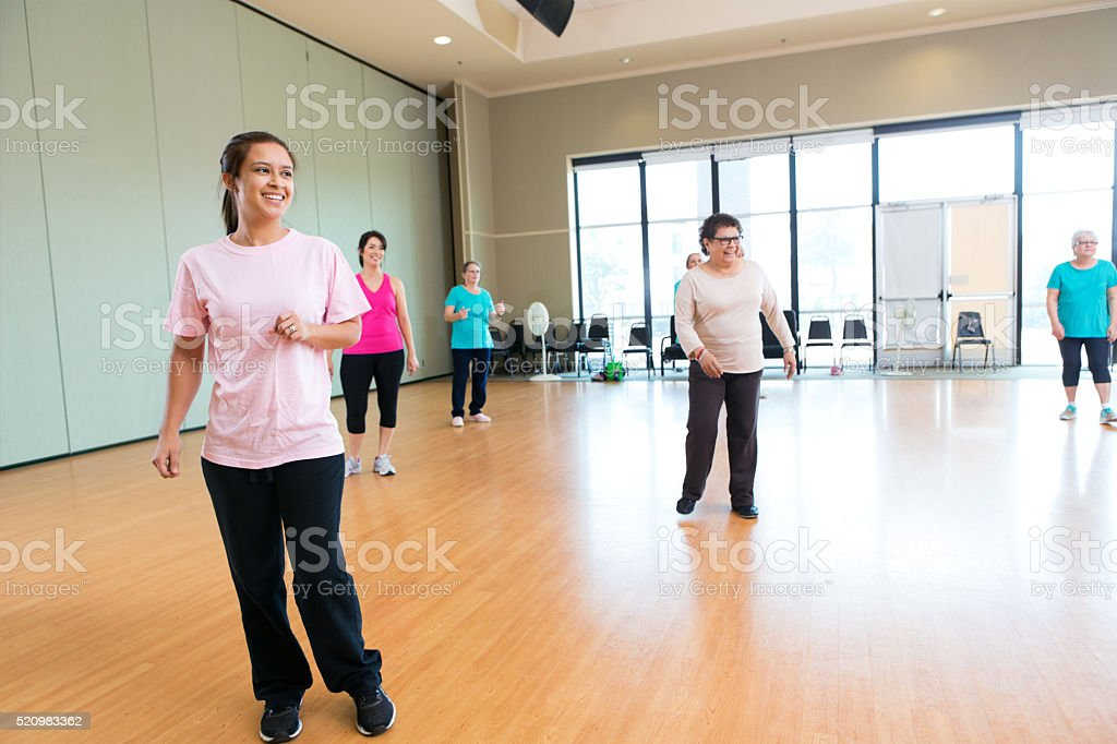 Group of diverse women enjoy themselves as they learn to line dance...