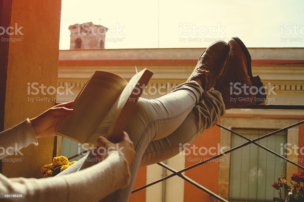 Women legs on balcony reading stock photo