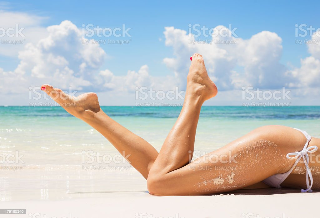 Women legs on the beach stock photo