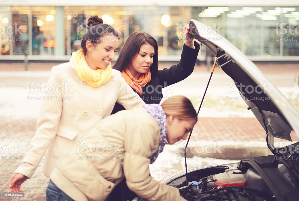 women look under the hood of a broken car stock photo