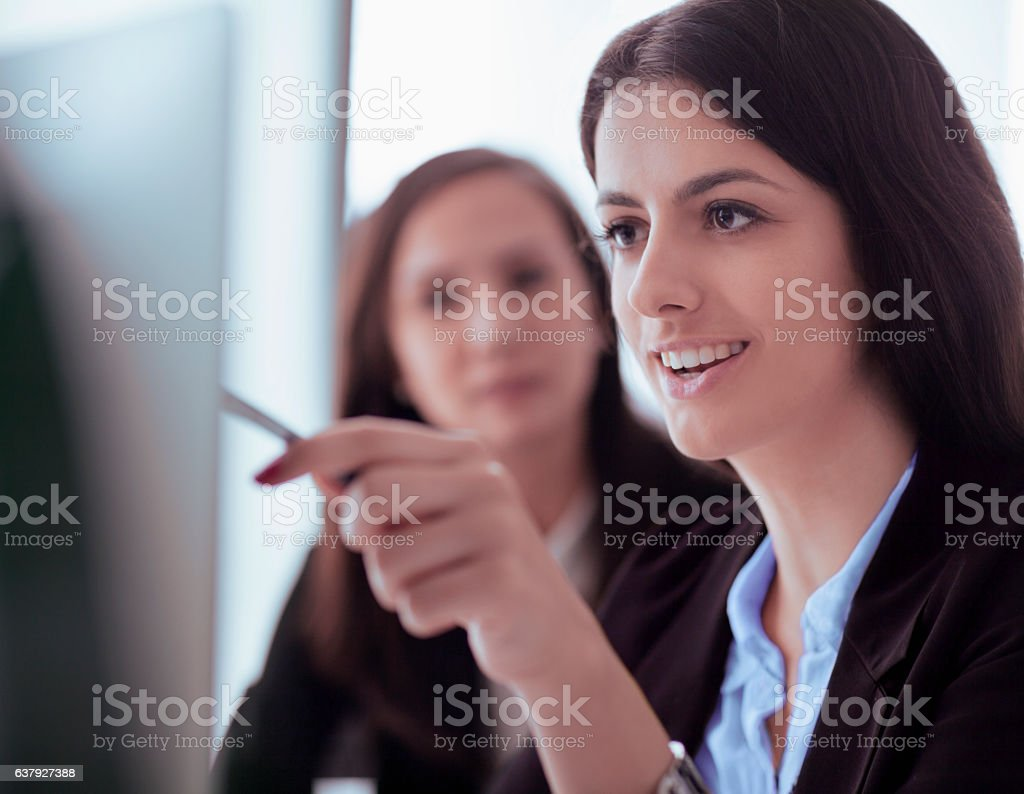 Women looking at computer screen in office stock photo