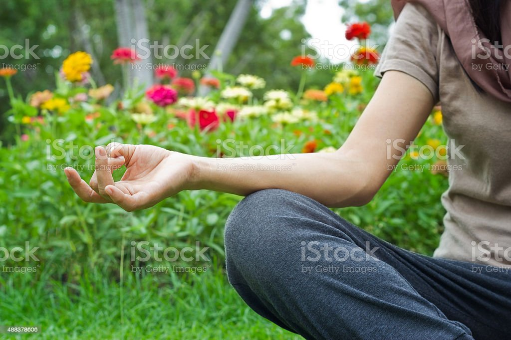 women meditating outdoors in flower park background stock photo