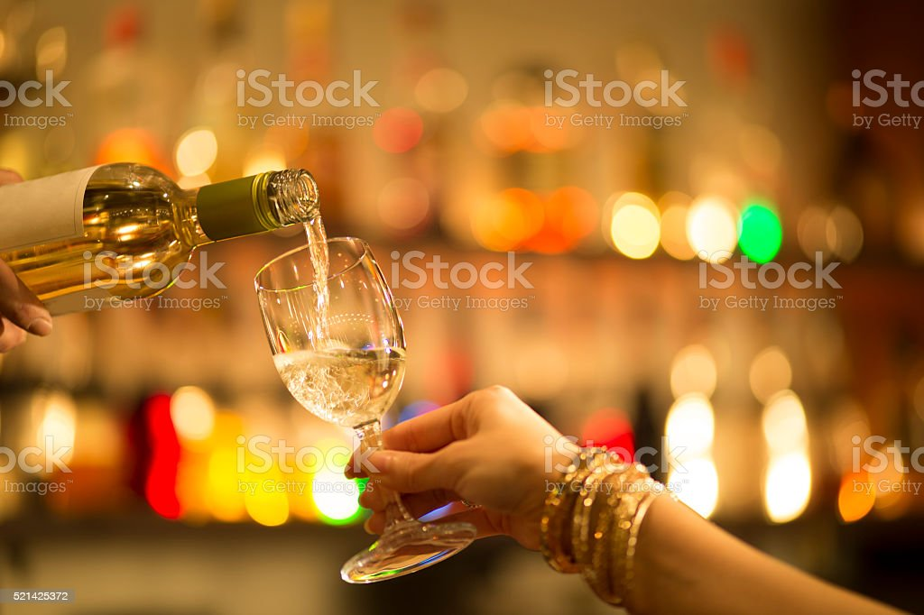 Women Mora pouring white wine at the bar stock photo