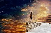 Women on dead end way high up on vast sky