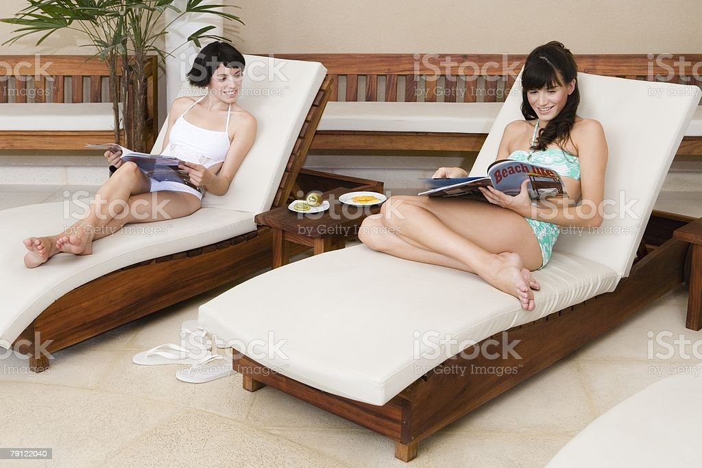 Women on lounge chairs with magazines royalty-free stock photo