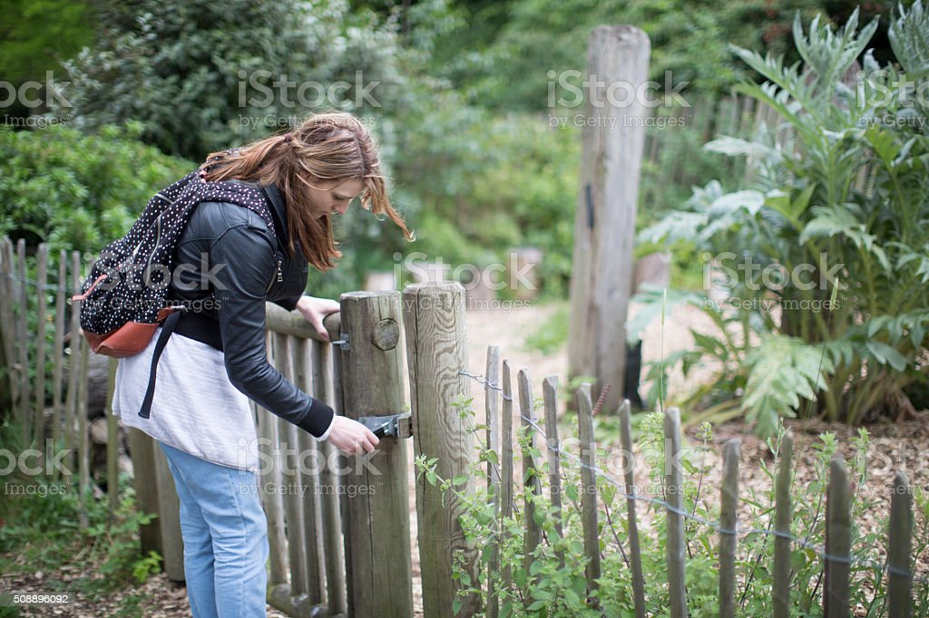 women opening garden gate stock photo