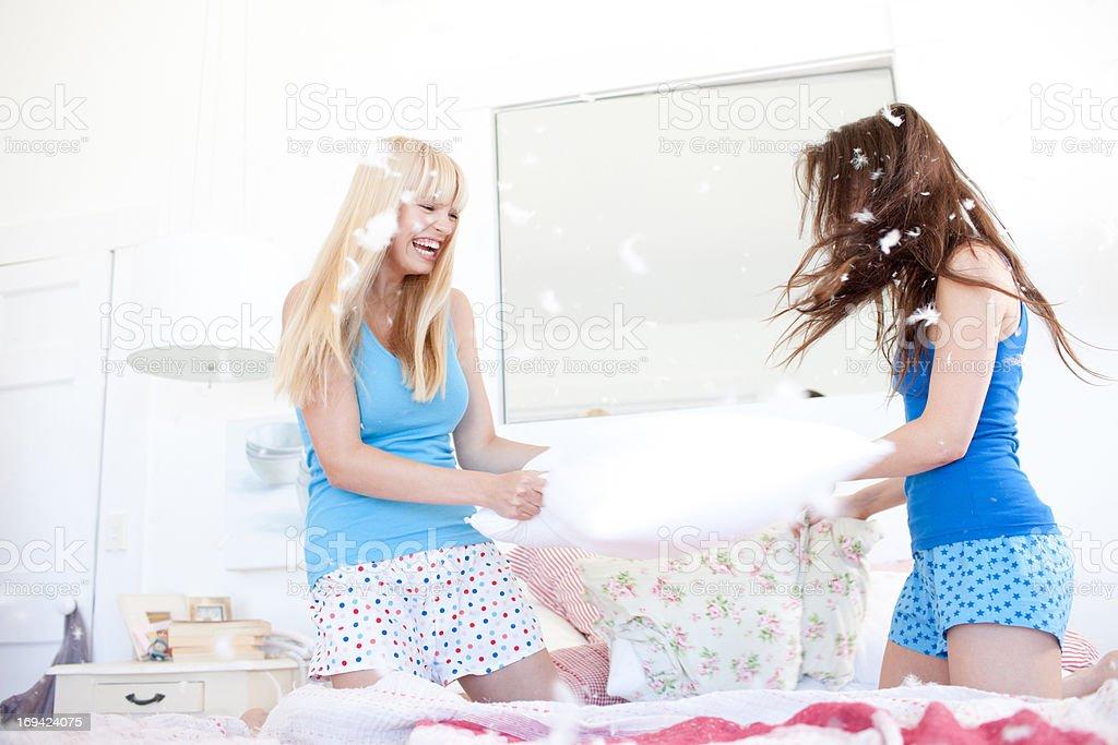Women pillow fighting in bedroom stock photo