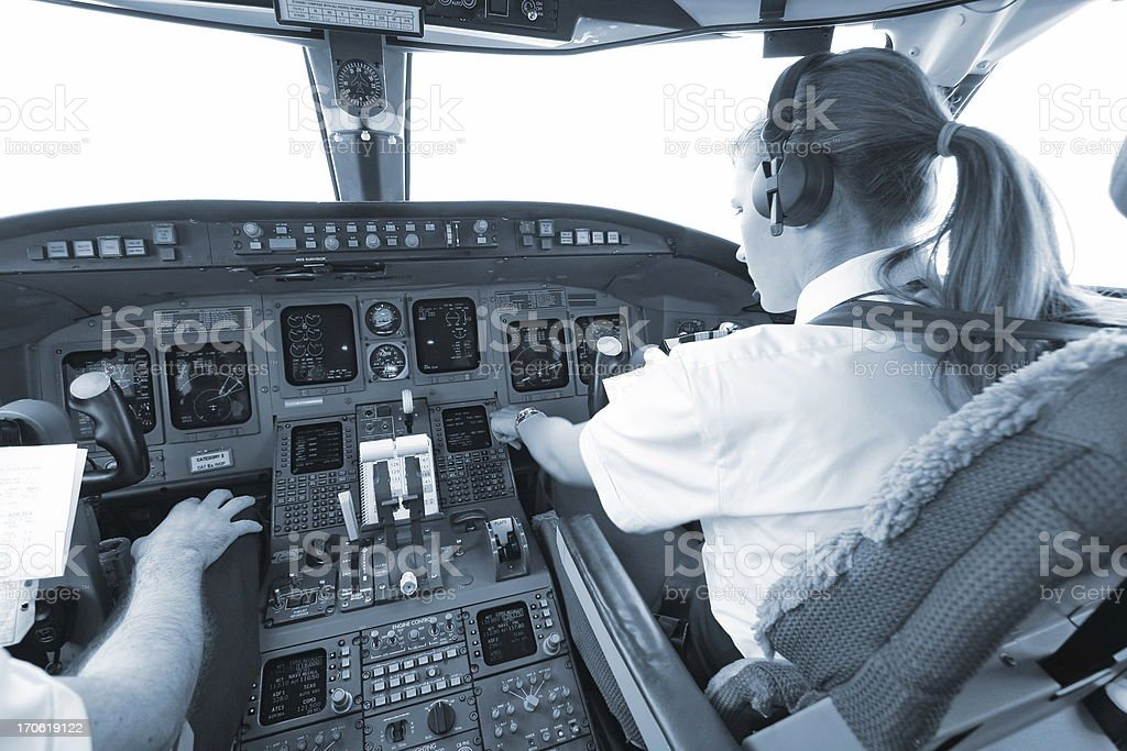 Women pilot above the clouds...cockpit of commercial jet stock photo