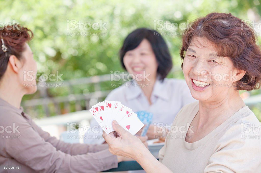 Women playing cards together stock photo