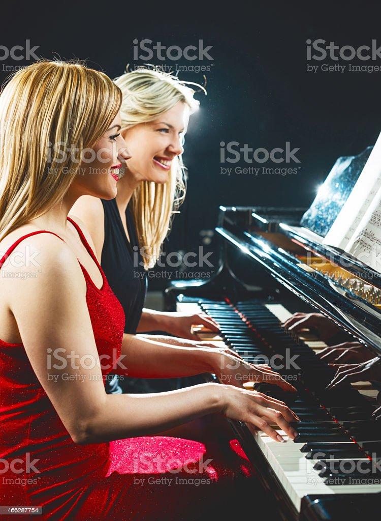 Women playing the piano. stock photo