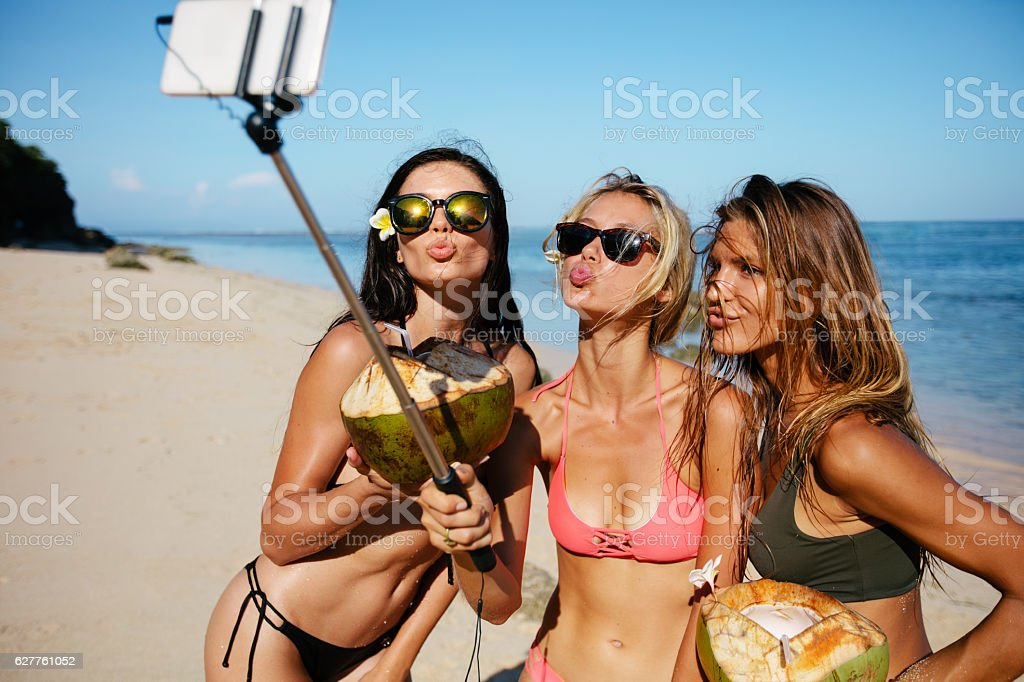 Women pouting for selfie on the beach stock photo