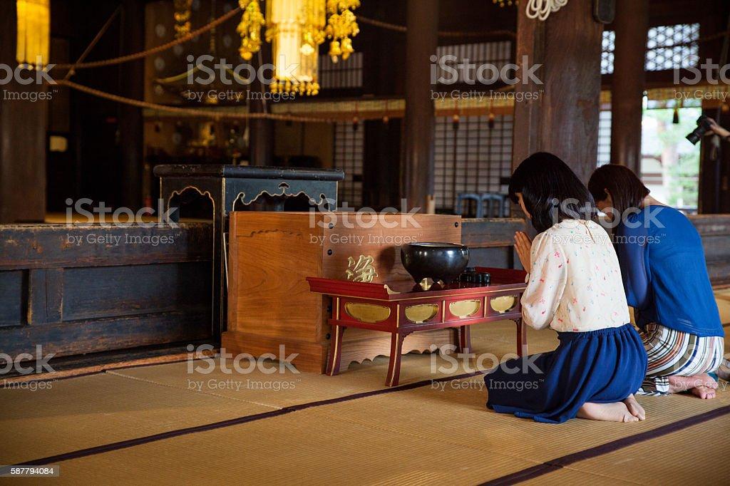 Women praying inside a Buddhist Temple stock photo