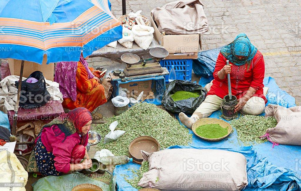 Women preparing spices inside Marrakech souk. Morocco. stock photo