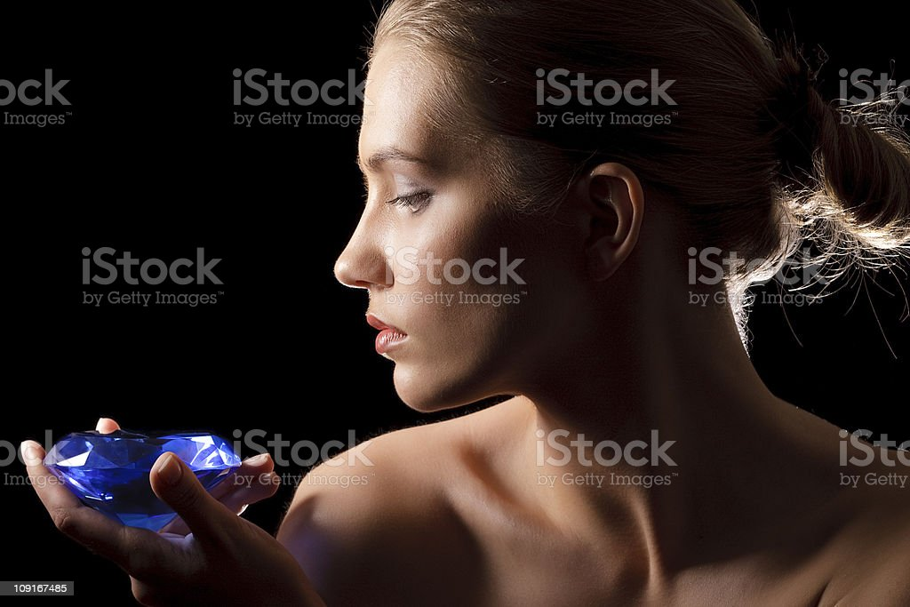 Women profile face and blue diamond in fingers stock photo