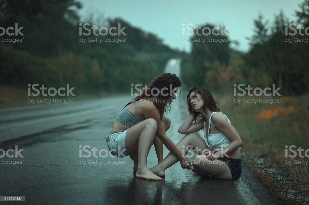 Women quarrel in  rain on the road. stock photo
