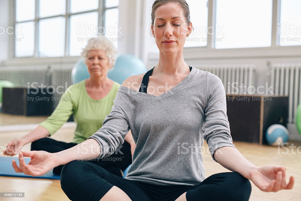 Women relaxing and meditating in their yoga class at gym stock photo