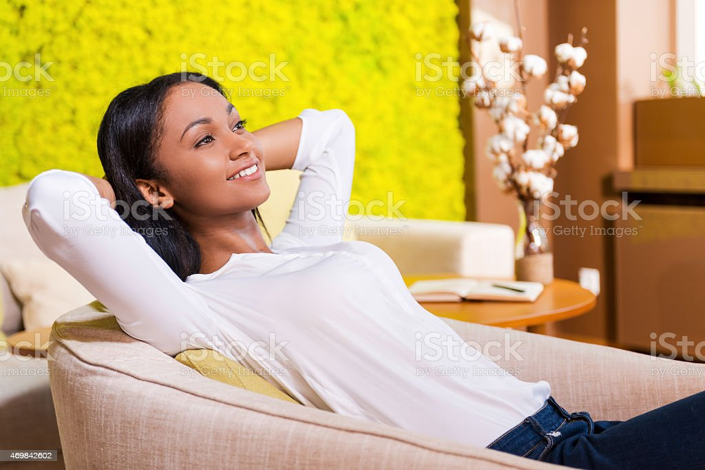 Women relaxing in a white chair in front of a yellow wall stock photo