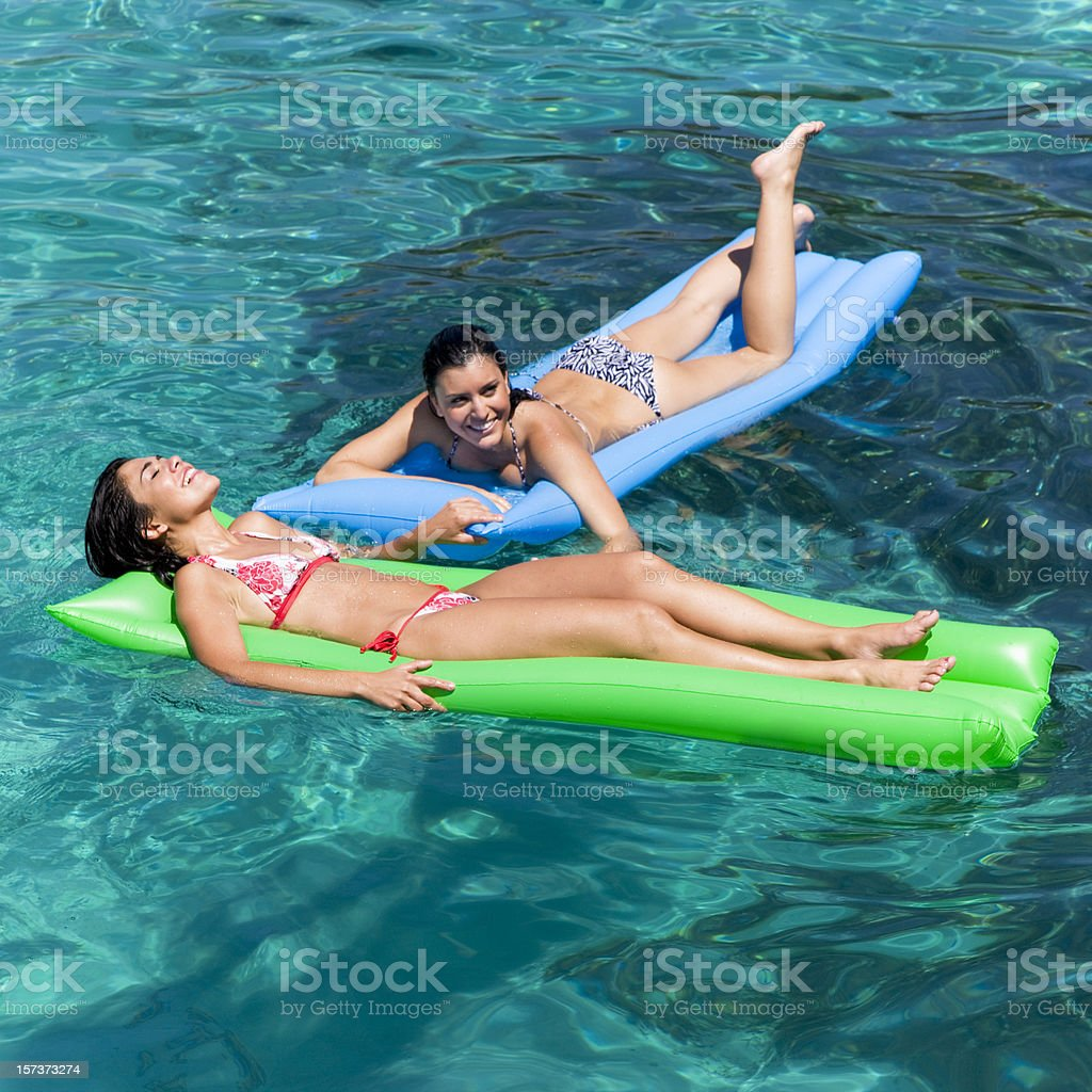 Women relaxing on an inflatable matress in blue lagoon royalty-free stock photo