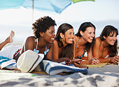 Women relaxing on beach blanket together
