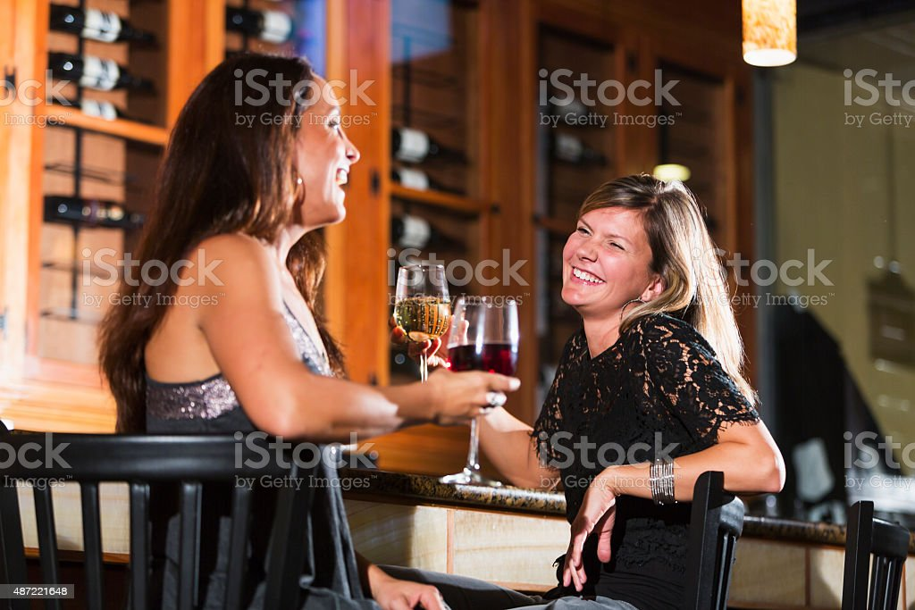 Women relaxing with glass of wine at restaurant bar stock photo