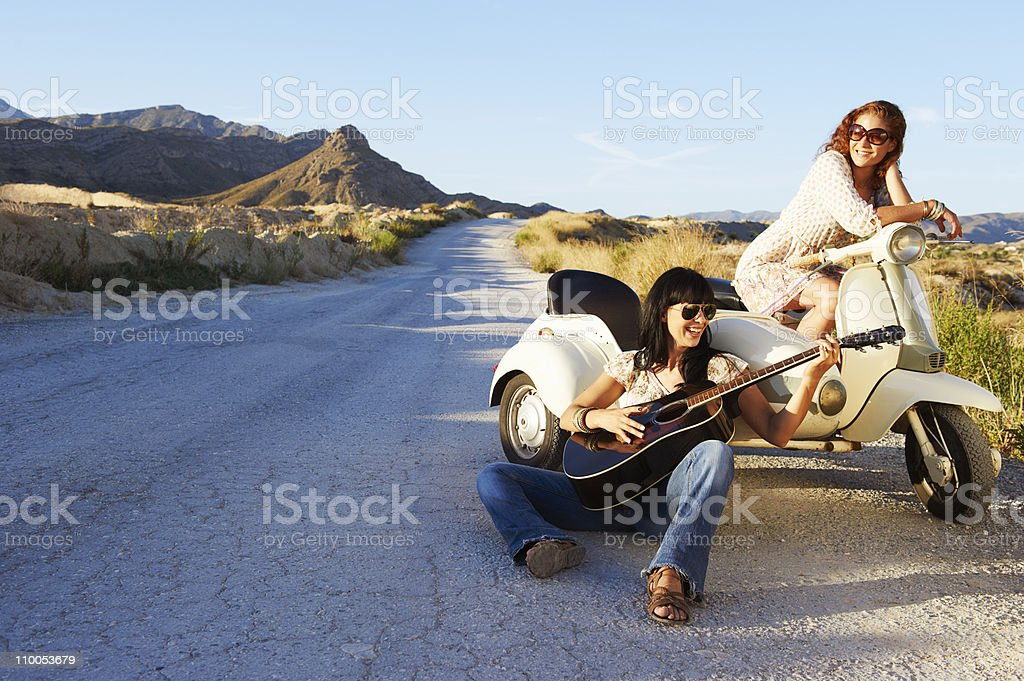 Women resting by road with motorbike stock photo