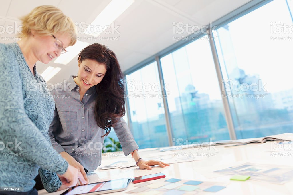 Women reviewing plans on tablet computer in studio stock photo