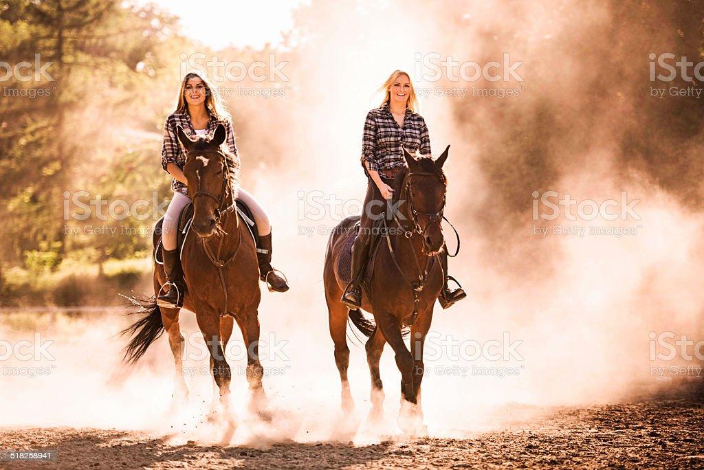 Women riding horses outdoors. stock photo