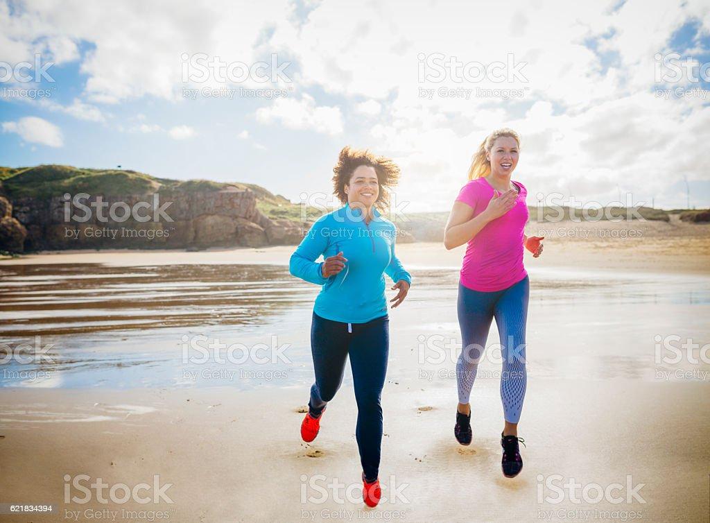 Women Running along a Beach Together stock photo