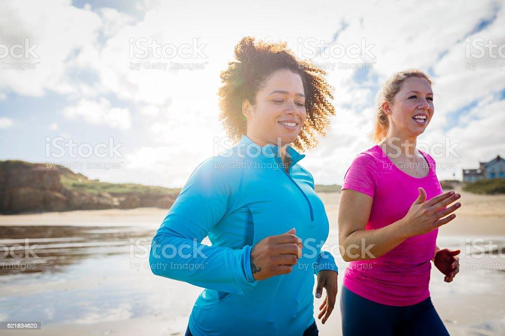 Women Running along the Shoreline stock photo