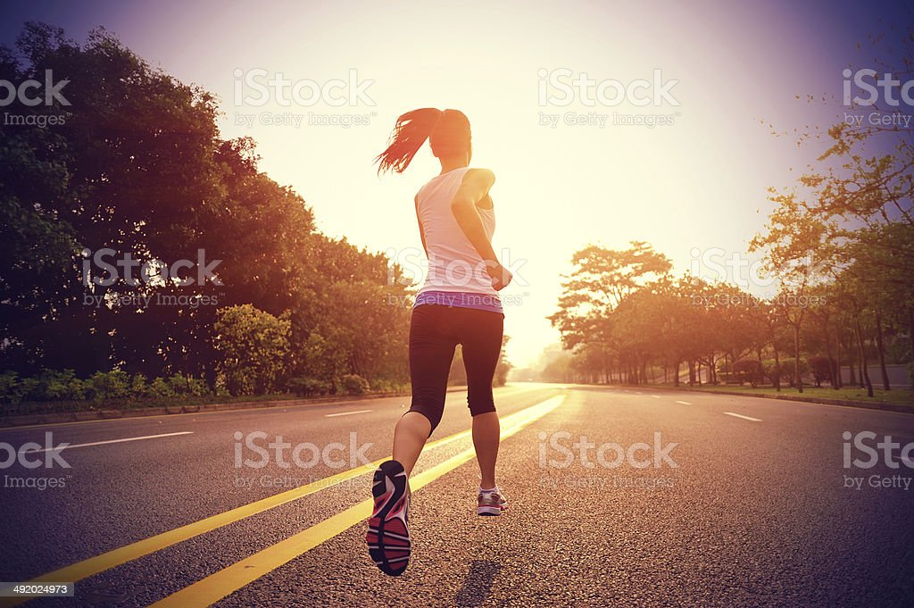 Women running on road in early morning stock photo