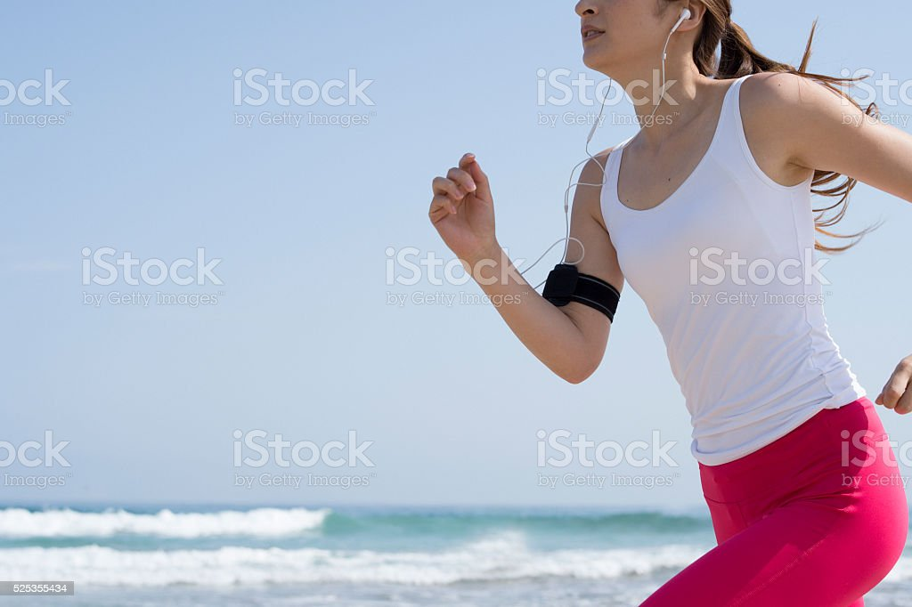 Women running while listening to music at the beach stock photo