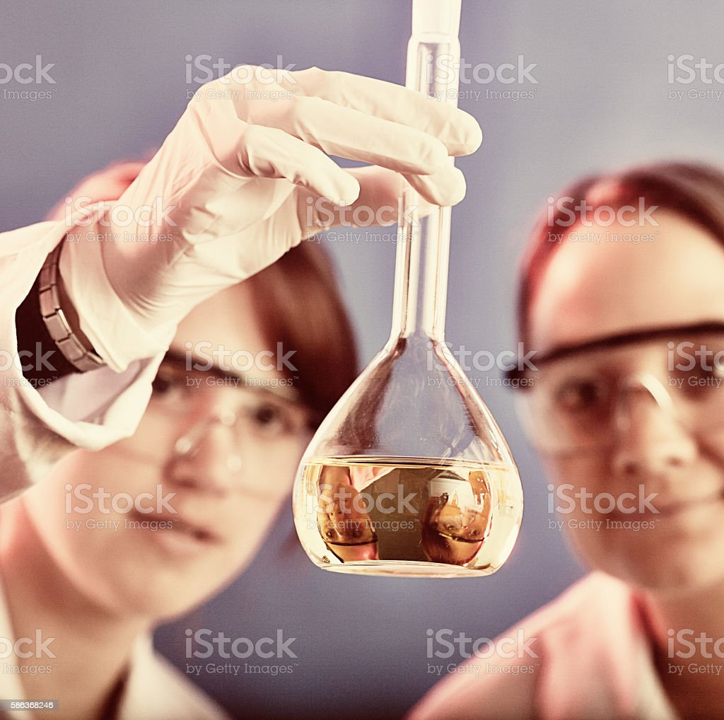 Women scientists in chemistry or biology laboratory examine flask stock photo