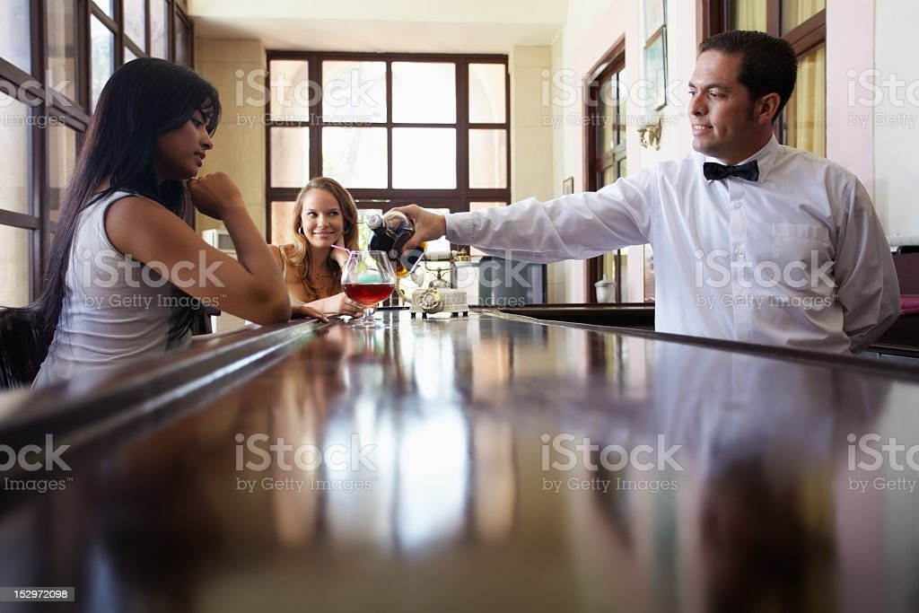 Women seated on bar drinking cocktail poured by bartender royalty-free stock photo