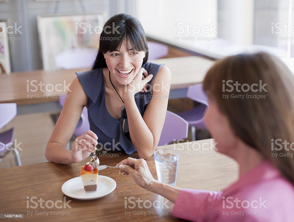 Women sharing dessert in cafe stock photo