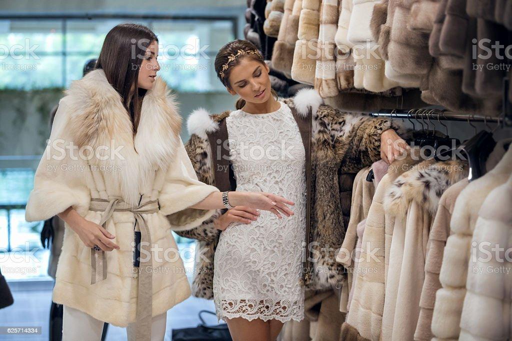 Women shopping for fur coat stock photo